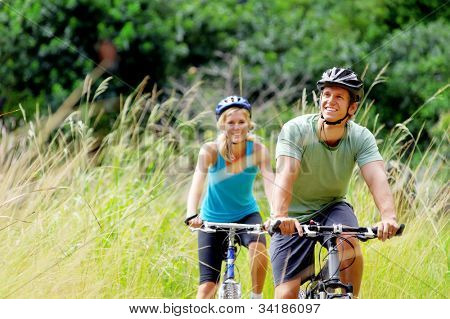 Happy couple riding bicycles outside, healthy lifestyle fun concept. mountain bike fitness outdoor exercise together