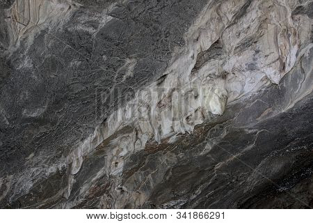 Gray Karst Cave. Rock Formations In The Cave, Stalactites And Stalagmites. Abstract Gray Grunge Back