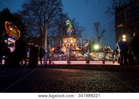 READING, UK - DECEMBER 27, 2019: Riders on a jump and smile thrill ride at a Christmas funfair in Reading, Berkshire, UK.
