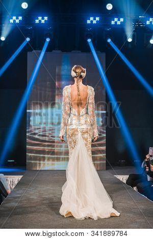 LJUBLJANA, SLOVENIA - OCTOBER 12, 2019: Fashion model in a wedding dress by Maja Ferme walking down the runway at the Wedding fair
