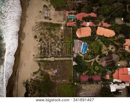 Aerial Shot Of A Beach Taken From The Coast Where The Waves Of The Sea Are Reaching A Beautiful Neig