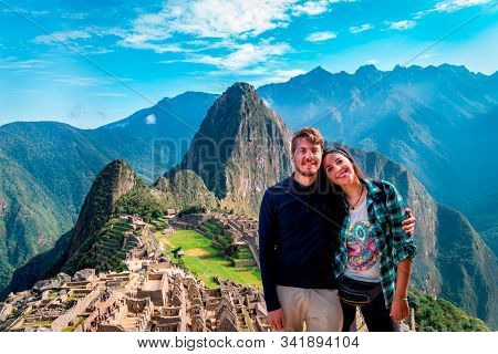 Young Couple Of Tourist In Machu Picchu. They Are Together, Happy And Relaxed. Behind, The City Of M