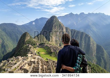 Young Couple Embracing Contemplating The Incredible Landscape Of Machu Picchu. The Ruins Of The Cita