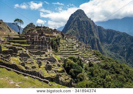 Machu Picchu City From The Inside. Huayna Picchu Mountain And Green Vegetation Can Be Seen. Cloudy D