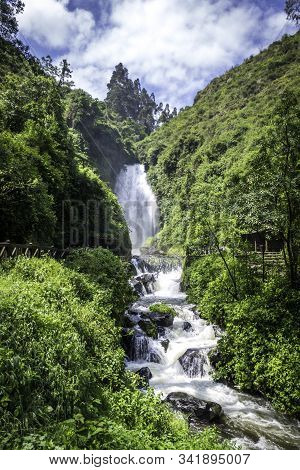 View Of Peguche Waterfall In The Mountains Of Ecuador. There Is A Huge Waterfall Surrounded By A Lot