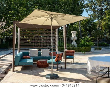 Modern Outdoor Furniture With Umbrella On Paved Marble Patio Or Courtyard