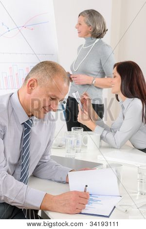 Mature businessman during team meeting with colleagues give presentation