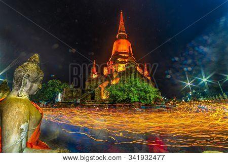 Unidentified Buddhists Making Candle Light Procession Around The Pagoda  In Wat Yai Chamongkon, The