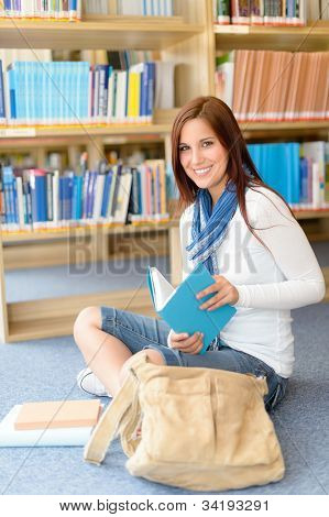 Female high school student sitting at library reading book