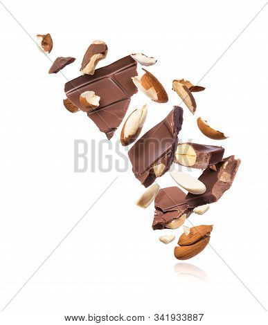 Pieces Of Chocolate Bar With Almonds Falling Down, Isolated On White Background