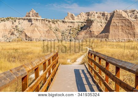 Panoramic View Of Badlands Geological Features With Bridge In Foreground