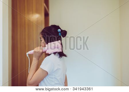 Asian Woman Using Electric Curling Iron With Hair In Bedroom,straightening Hair,straightener