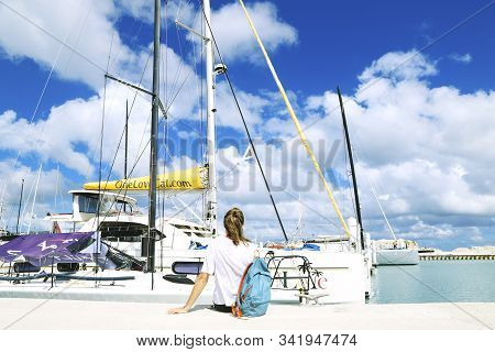 Tortola British Virgin Islands - March 28, 2018 - Young Girl Sitting On A Pier Enjoying The View Of