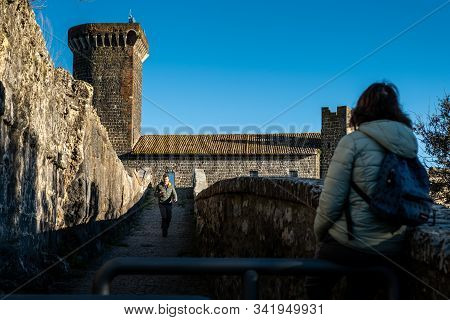 Vulci, Italy - December 26, 2019: Two Unknown Tourist At The Badia Bridge And Castle, Medieval Datin