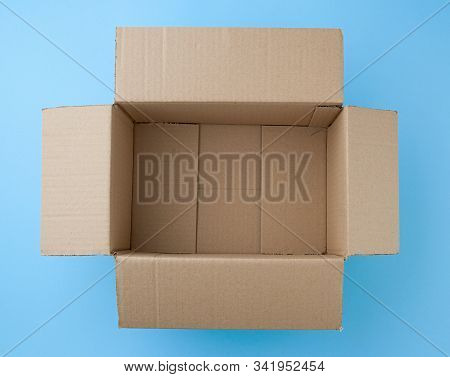 Open Empty Square Brown Cardboard Box For Transportation And Packaging Of Goods On Blue Background,