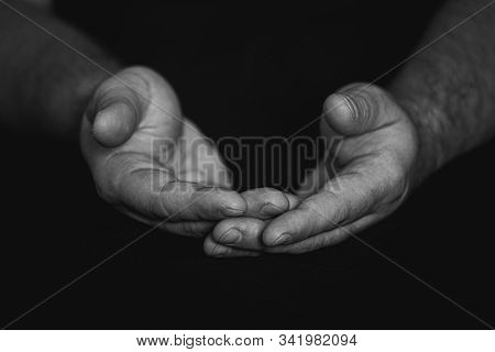 Low Key, Close Up Of Hands Of A Faithful Mature Man Praying, Hands Folded, Interlaced Fingers In Wor