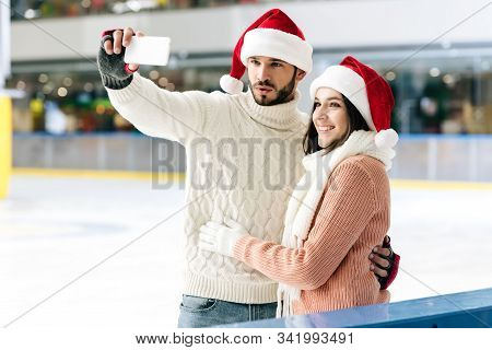 Cheerful Couple In Santa Hats Taking Selfie On Smartphone On Skating Rink At Christmastime