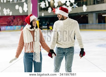 Beautiful Happy Couple In Santa Hats Holding Hands At Christmastime On Skating Rink
