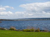 Landscape Lake Washington and 520 bridge in Seattle Washington.  Blue skies and white puffy clouds and green grass foreground in this travel destination. poster