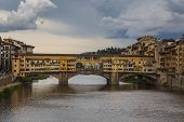 The Ponte Vecchio, a medieval stone closed-spandrel segmental arch bridge over the Arno River, in Florence, Italy, noted for still having shops built along it. poster