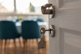 Open Door To A New Home. Door Handle With Key And Home Shaped Keychain. Mortgage, Investment, Real E