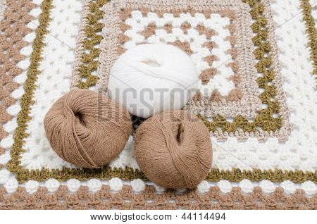 Square knitted carpet with yarn balls on white poster