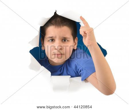Angry boy looking through paper hole isolated on white background