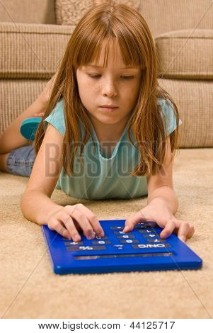 Young female child works on an over-sized calculator