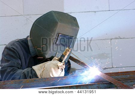 welder worker welding metal. Bright electric arc and sparks poster