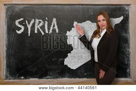 Teacher Showing Map Of Syria On Blackboard