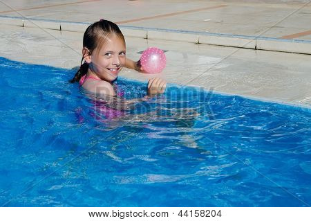 Happy Girl In The Pool With Ball