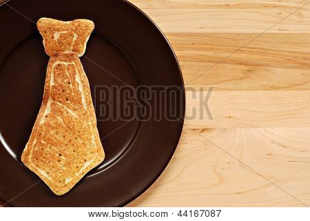 Father's day background image with real pancake in the shape of a necktie on plate.  Closeup with wood background and copy space.