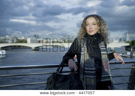 portrait of young thoughtful curl girl standing on the bridge. London. UK
