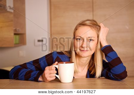 Young woman enjoying her tea break in a kitchen poster