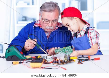 Grandfather Explaining To Grandchild How Soldering Works