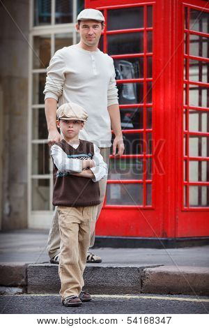 Happy father and son outdoors in city by red phone booth poster