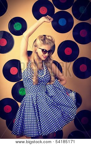 Charming pin-up woman with retro hairstyle and make-up posing with vinyl record. poster