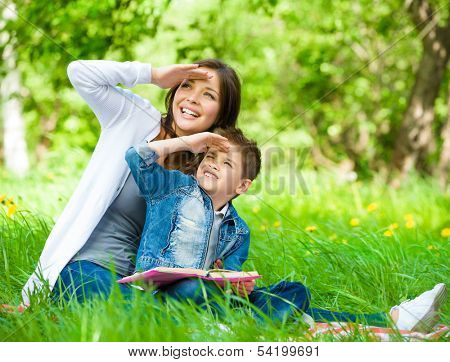 Mother and son with book sitting on green grass cover eyes from sun in park. Concept of happy family relations and carefree leisure time