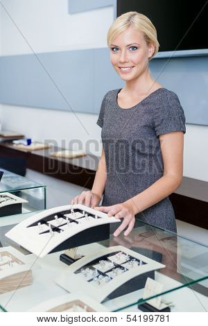 Salesperson at the window case with rings at jeweler's shop. Concept of wealth and luxurious life