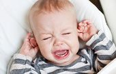 cute little boy crying and holding his ear on a white background poster