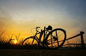 Beautiful landscape of nature with impression 's sun and silhouette of bicycle put up at wooden fence in sunrise at countryside poster