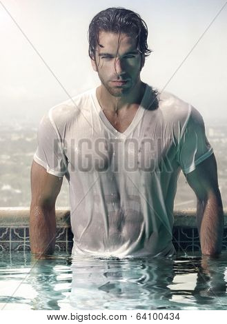 Gorgeous male model in soaked wet t-shirt standing in luxurious swimming pool with city background