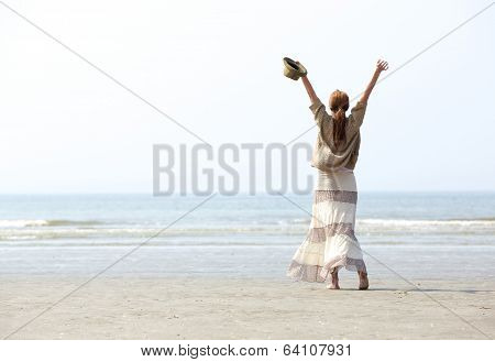 Woman With Raised Arms At The Beach