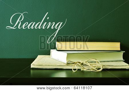 the word reading and a pile of books on a desk