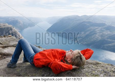 Woman hiker relaxing / lying down on Pulpit Rock / Preikestolen, Norway. Pulpit rock is a massive cliff 604 metres above Lysefjorden, almost flat, and is a famous tourist attraction in Norway. poster