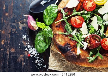 pizza and fresh italian ingredients on a dark background