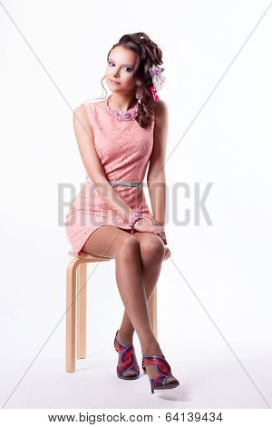 Pretty Brunette In A Pink Dress Sitting On A Chair On A White Background
