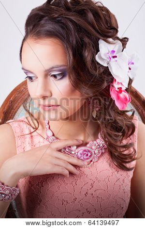 Gentle Woman In A Pink Dress And A Pink Necklace Thoughtful