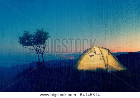 Night landscape with a tent in the mountains. The light from the lantern in a tent. Camping in the countryside. Crimea, Ukraine, Europe. Filtered image: vintage, grunge and texture effects