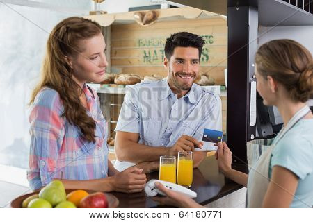 Side view of a couple paying bill at coffee shop using card bill